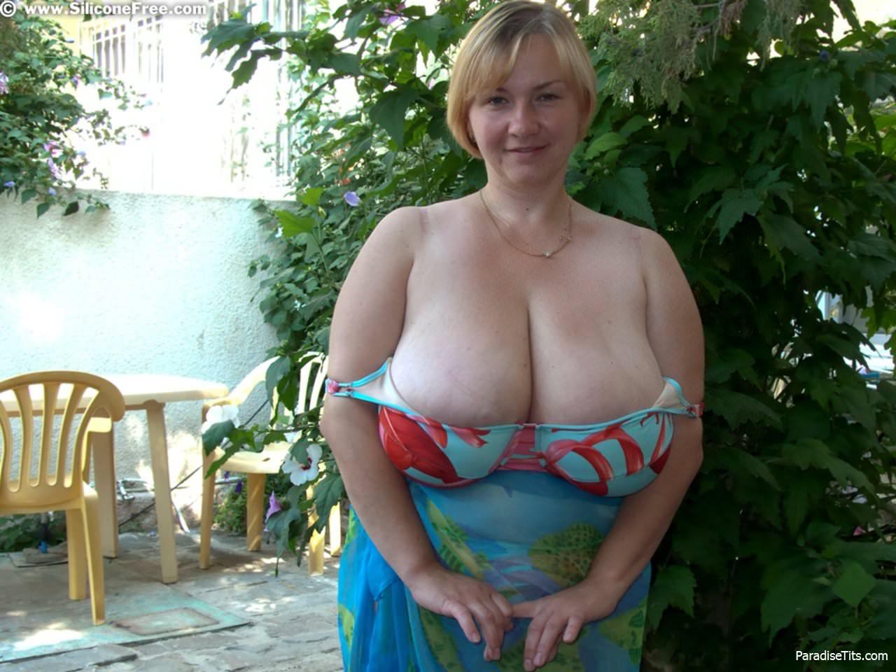 Зрелая рыжая блядь на порно фото сексуально сжимает огромные сисяндры в руках