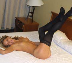 Порно фото, где блондинка в черных чулках лапает себя на кровати
