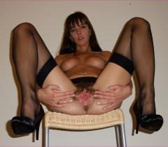 Порно фото, где стройная брюнетка демонстрирует волосатую пизду в разных комплектах чулков