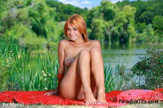 Рыжая чертовка на порно фото игриво извивается в обнаженном виде на фоне природы