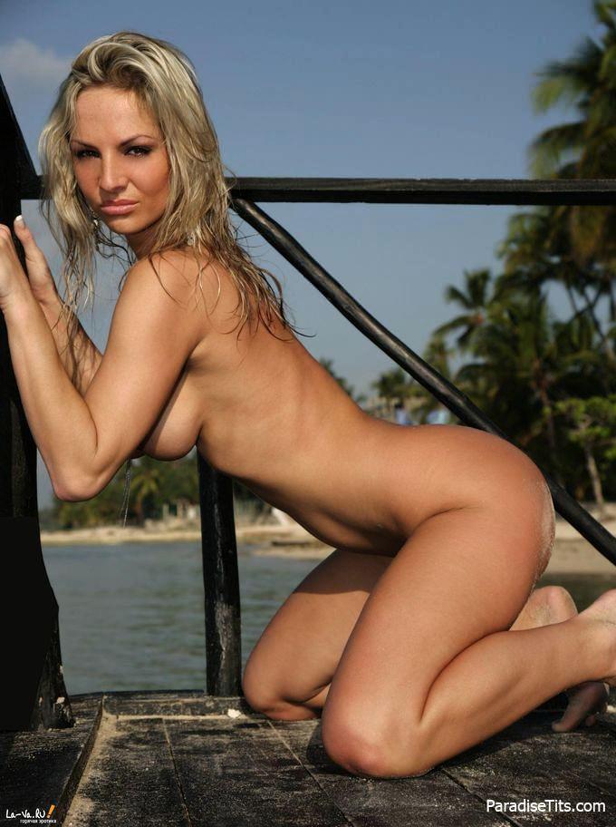 Голая блондинка нагибается и показывает пизду на порно фото