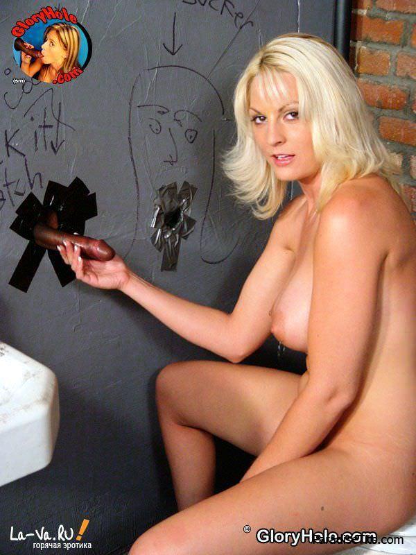 На фото светловолосая барышня делает парню реальный минет через дырочку в стене, получая сперму на личико