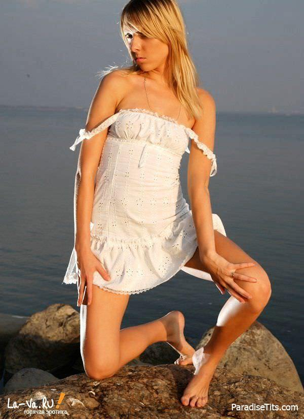 На качественных фото красивая девушка сняла платье и трусики, чтобы покрутить пиздой на живописном фоне моря